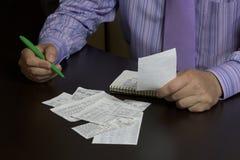 L'homme compte le coût de chèques ordinaires Un budget de famille Images stock