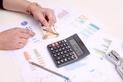 L'homme compte le nouvel Indien devise de 10 roupies Photo de calculatrice, de papier de diagramme, d'agrafeuse et de crayon photographie stock libre de droits