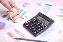 L'homme compte le nouvel Indien devise de 10 roupies Photo de calculatrice, de papier de diagramme et de crayon image libre de droits