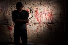 L'homme concentré tenant une faucille tenant le sang proche a souillé le wa photographie stock