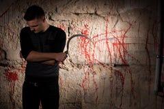 L'homme concentré tenant une lame tenant le sang proche a souillé wal photos libres de droits