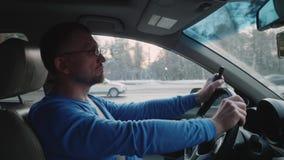 L'homme conduit la voiture rapidement et essaye de composer le téléphone de bouton ON de nombre banque de vidéos