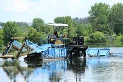 L'homme conduit une moissonneuse de végétation de lac Photographie stock libre de droits