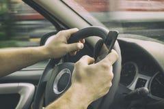 L'homme conduit une voiture et tient un téléphone portable image stock