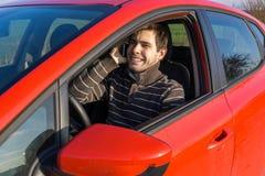 L'homme conduit une voiture, tient le téléphone et appeler avec quelqu'un Images libres de droits
