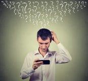 L'homme confus regardant son téléphone intelligent mobile a beaucoup de questions Images stock