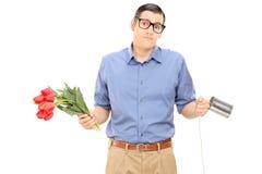 L'homme confus tenant des fleurs et une boîte en fer blanc téléphonent Photographie stock