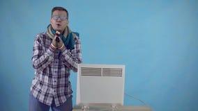 L'homme congelé couvert de gel et de gants chauffe à côté d'un radiateur électrique sur un fond bleu banque de vidéos
