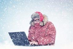 L'homme congelé en hiver rouge vêtx travailler sur un ordinateur portable de la neige Froid, gel, tempête de neige image libre de droits