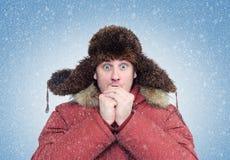L'homme congelé en hiver vêtx les mains de chauffage, froid, neige, tempête de neige photo libre de droits