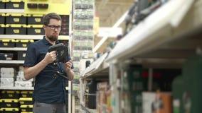 L'homme considère un puzzle dans un hypermarché des outils de bâtiment banque de vidéos