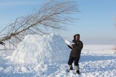 L'homme construisant un igloo sur une clairière de neige pendant l'hiver Photographie stock libre de droits