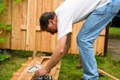 L'homme construisent une frontière de sécurité en bois photos stock