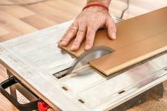 L'homme coupant les panneaux de plancher en stratifi? sur la circulaire a vu, d?tail sur des mains tenant le panneau en bois images libres de droits