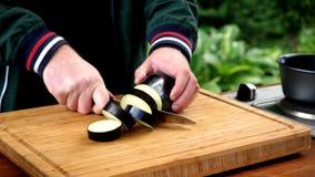 L'homme coupe l'aubergine de tranches sur la planche à découper photo libre de droits