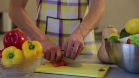 L'homme coupe la tomate dans la cuisine banque de vidéos