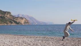 L'homme court sur la plage près de la mer avec un petit jouet d'avion clips vidéos