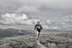 L'homme court sur le pré vert en montagne sur le ciel nuageux images stock