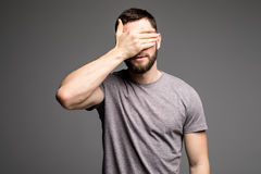 L'homme couvre son visage photographie stock