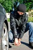 L'homme crève un pneu de véhicule. Photo stock