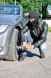 L'homme crève un pneu de véhicule. Photographie stock libre de droits