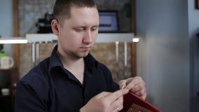 L'homme crée un portefeuille en cuir brun avec ses propres mains avec une aiguille dans l'atelier en cuir clips vidéos