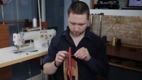 L'homme crée un portefeuille en cuir brun avec ses propres mains avec une aiguille dans l'atelier en cuir banque de vidéos
