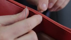 L'homme crée un portefeuille en cuir brun avec ses propres mains avec une aiguille dans l'atelier en cuir, plan rapproché clips vidéos