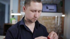 L'homme crée un portefeuille en cuir brun avec ses propres mains avec une aiguille dans l'atelier en cuir, plan rapproché banque de vidéos