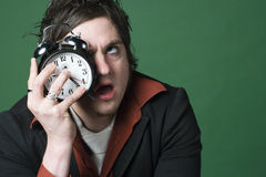 L'homme craint son horloge d'alarme photographie stock libre de droits