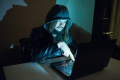 L'homme criminel obscur essaye d'entailler le système photos stock