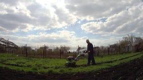 L'homme cultive la terre dans le jardin avec une talle, pr?parant le sol pour l'ensemencement banque de vidéos