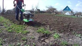 L'homme cultive la terre dans le jardin avec une talle, pr?parant le sol pour l'ensemencement clips vidéos