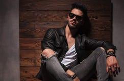L'homme décontracté de mode dans les lunettes de soleil et la veste en cuir s'assied photos libres de droits