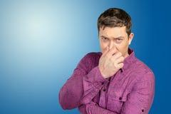 L'homme dégoûté pince le nez avec des doigts Photos stock