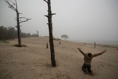 L'homme déprimé n a sur Lap Raised Hands Up Against le fond des arbres morts image stock