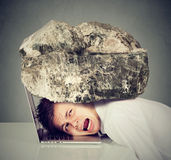 L'homme désespéré d'affaires avec la tête a serré entre l'ordinateur portable et la roche images stock