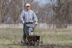 L'homme détache le cultivateur de sol Image libre de droits
