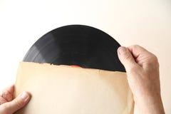 L'homme détient le disque vinyle dans la douille Image libre de droits