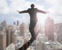 L'homme d'affaires équilibrant sur un fil avec le ciel opacifie le paysage urbain Image stock