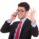 L'homme d'affaires affiche se connectent normalement le téléphone Photo libre de droits
