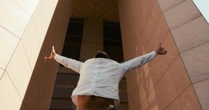 L'homme d'affaires africain enthousiaste attirant soulevant heureusement ses mains lèvent extérieur longueur 4k banque de vidéos