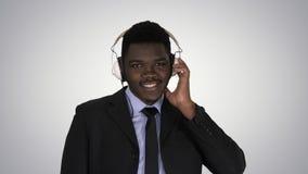 L'homme d'affaires afro-américain bel dans des écouteurs écoute la musique sur le fond de gradient photos libres de droits