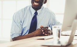 L'homme d'affaires afro-américain bel dans le costume classique utilise un ordinateur portable et sourit tout en travaillant dans photos libres de droits