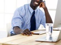 L'homme d'affaires afro-américain bel dans le costume classique utilise un ordinateur portable et sourit tout en travaillant dans image libre de droits