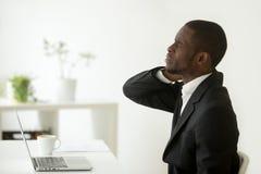 L'homme d'affaires d'afro-américain sent des douleurs articulaires de cou raide après s photos stock