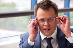 L'homme d'affaires ajuste ses verres Photos libres de droits
