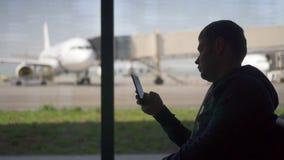 L'homme d'affaires américain d'homme de silhouette à l'aide du téléphone à l'aéroport regarde l'appli dans le téléphone banque de vidéos