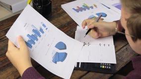 L'homme d'affaires analyse des diagrammes et écrit dans un bloc-notes clips vidéos
