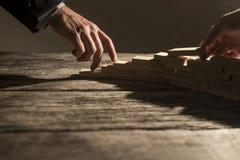 L'homme d'affaires arrangeant les chevilles en bois dedans à un escalier aiment le structu Image libre de droits
